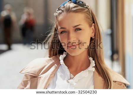 Portrait of a young beautiful lady in a sunny cityscape - stock photo