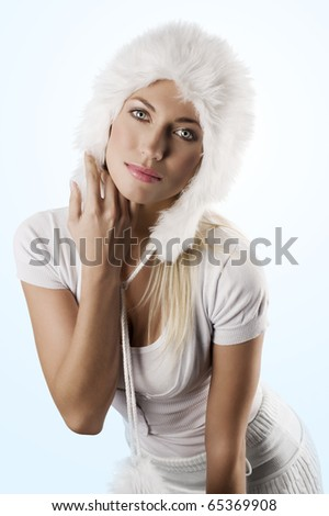 portrait of a young beautiful model in white winter dress with a nice fur hat - stock photo