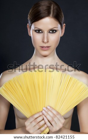 Portrait of a young beautiful naked woman holding a fan of spaghetti in front of her - stock photo