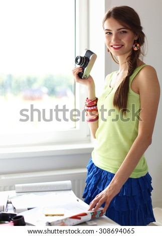 Portrait of a young beautiful photographer woman on the table