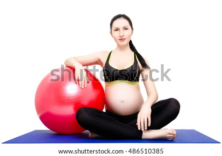 Portrait of a young beautiful pregnant woman, sitting on yoga mat with fitball, isolated on white background