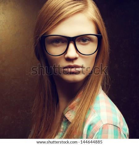 Portrait of a young beautiful red-haired student girl wearing trendy glasses and casual shirt and posing over golden background. Hipster style. Close up. Studio shot