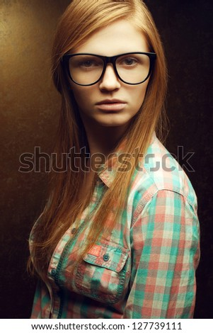 Portrait of a young beautiful red-haired wearing trendy glasses and casual shirt and posing over golden background. Close up. Studio shot. - stock photo