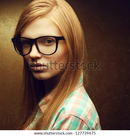 Portrait of a young beautiful red-haired wearing trendy glasses and casual shirt and posing over golden background. Close up. Copy-space. Studio shot.