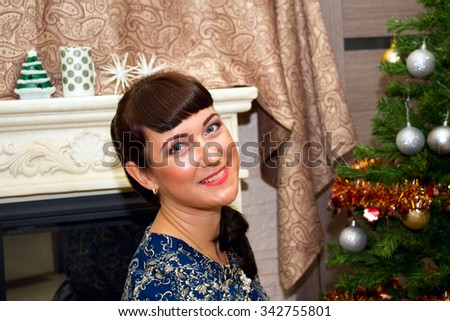 Portrait of a young beautiful smiling woman near a Christmas tree.