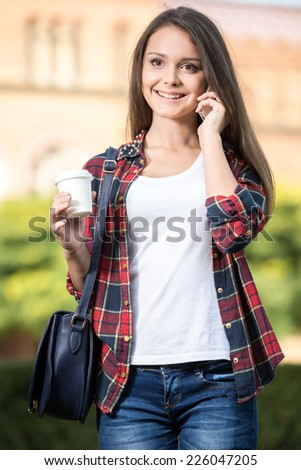 Portrait of a young beautiful student with university building in the background. She is saying by phone. - stock photo