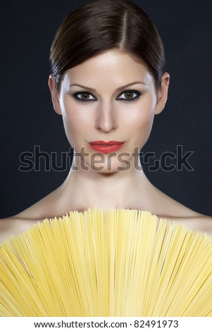 Portrait of a young beautiful woman holding a fan of spaghetti in front of her