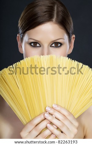 Portrait of a young beautiful woman holding a fan of spaghetti in front of her face with both hands - stock photo