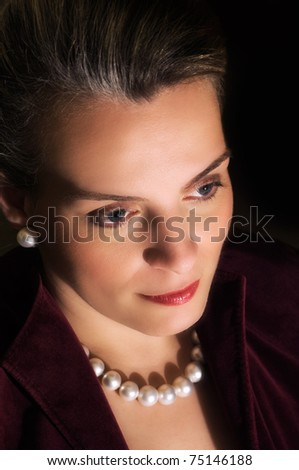 Portrait of a young beautiful woman in evening clothing and jewels - stock photo