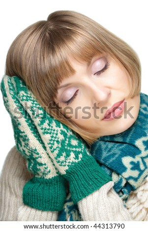 Portrait of a young beautiful woman in mittens and scarf with eyes closed, isolated on white - stock photo