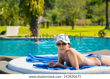 Portrait of a young beautiful woman in white cap and sunglasses lying on a sun lounger on against the background of the pool background. The concept of leisure and tourism