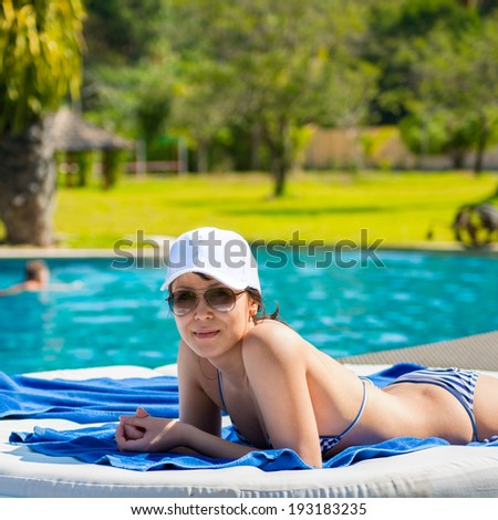 Portrait of a young beautiful woman in white cap and sunglasses lying on a sun lounger on against the background of the pool background. The concept of leisure and tourism - stock photo