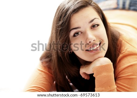 Portrait of a young beautiful woman lying on the bed with a copyspace. - stock photo