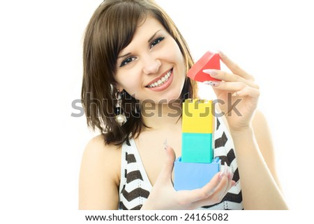 portrait of a young beautiful woman making a toy house - stock photo