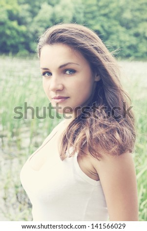 Portrait of a young beautiful woman on nature - stock photo