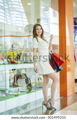 Portrait of a young beautiful woman on the background showcases a shoe store - stock photo