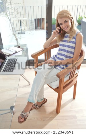 Portrait of a young beautiful woman sitting and smiling in home office space using a smartphone to have a call conversation. Student using a laptop computer. Lifestyle and technology, interior. - stock photo