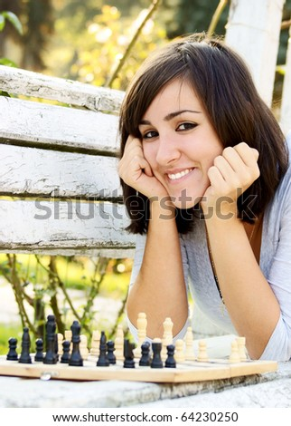 Portrait of a young beautiful woman smiling while playing a game of chess - stock photo