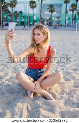 Portrait of a young beautiful woman taking self picture with smart phone while sitting on the seashore, female tourist using mobile phone camera for take a picture of herself during vacation holidays