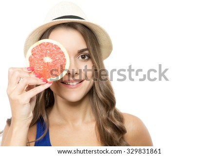 Portrait of a young beautiful woman wearing a hat posing, holding a piece of a grapefruit in front of her eye, isolated on white background