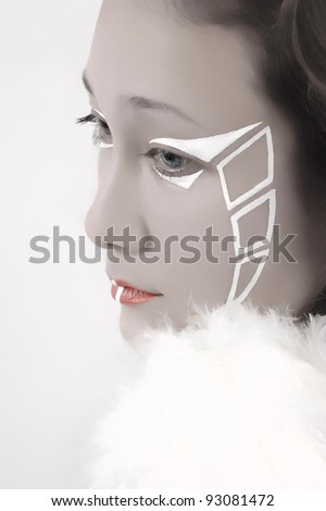 Portrait of a young beautiful woman with artistic makeup and white feathers - stock photo