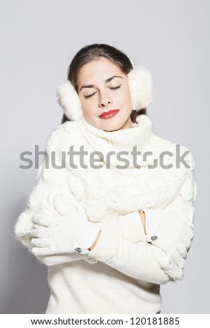 portrait of a young beautiful woman with close eyes, total white winter look. on grey background. - stock photo