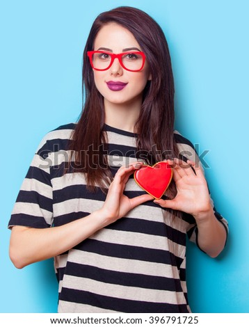 portrait of a young beautiful woman with cookie standing on the blue background - stock photo