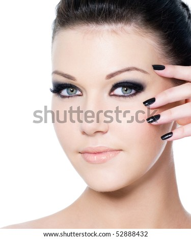 portrait of a young beautiful woman with fashion black make-up and manicure - isolated on white - stock photo