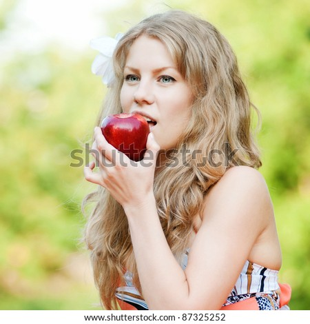 Portrait of a young beautiful woman with red apple at park