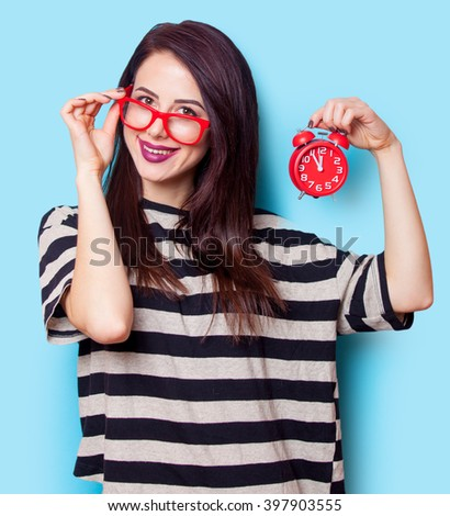portrait of a young beautiful woman with red clock standing on the blue background - stock photo