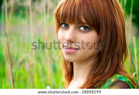 Portrait of a young beautiful woman with red hair
