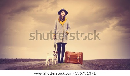 portrait of a young beautiful woman with suitcase and dog standing in the field - stock photo