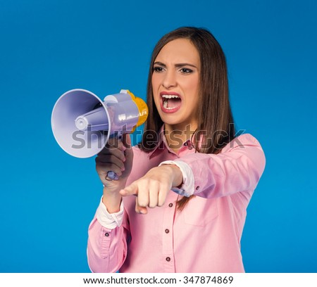 Portrait of a young beautiful woman yelling into a megaphone on blue background - stock photo