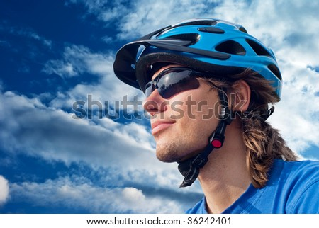 portrait of a young bicyclist in helmet and glasses on a sky background - stock photo