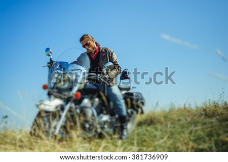 Portrait of a young biker with beard sitting on his cruiser motorcycle and looking to his bike. Man is wearing leather jacket and blue jeans. Low point of view. Tilt shift lens blur effect - stock photo
