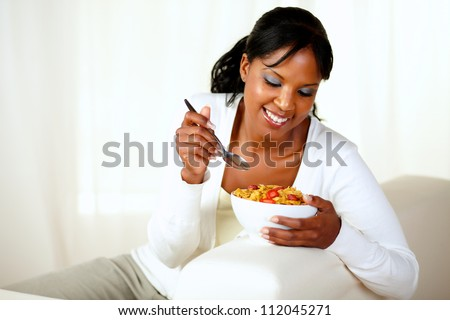 Portrait of a young black female having healthy breakfast while is sitting on couch at home indoor. with copyspace - stock photo