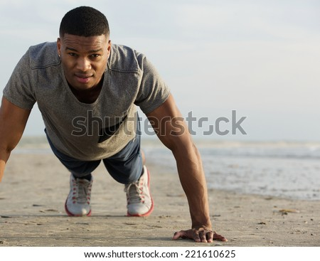Portrait of a young black man doing push ups at the beach - stock photo