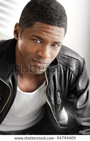 Portrait of a young black man in leather jacket against modern bright background - stock photo