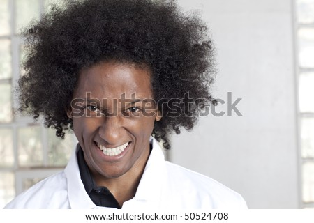 Portrait of a young black man with an afro and a lab coat grinning crazily at the camera. Horizontal format. - stock photo