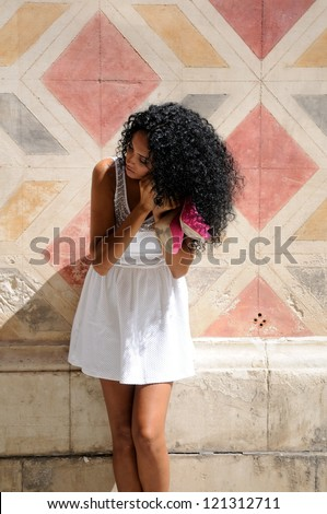 Portrait of a young black woman, afro hairstyle, getting dressed in the street
