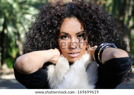 Portrait of a young black woman, afro hairstyle, in urban background - stock photo