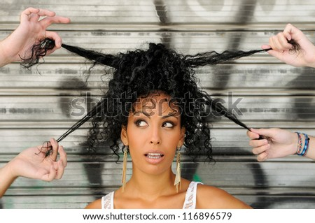 Portrait of a young black woman, afro hairstyle, in urban background with four hands playing with her hair - stock photo