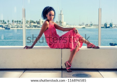 Portrait of a young black woman, afro hairstyle, wearing long pink dress, in the harbor - stock photo