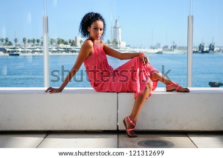 Portrait of a young black woman, afro hairstyle, wearing long pink dress, in the harbour - stock photo