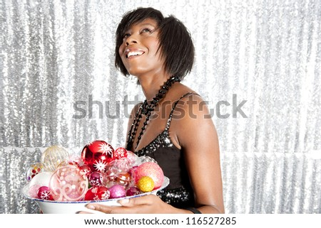Portrait of a young black woman holding a dish full of christmas bar balls against a silver sequins background.