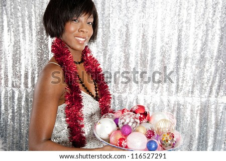 Portrait of a young black woman holding a dish full of Christmas bar balls tree decorations and wearing a strip of tinsel around her neck while standing in front of a silver sequins background. - stock photo