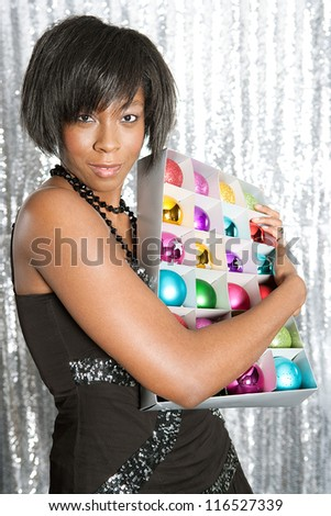 Portrait of a young black woman hugging a box with different color christmas balls decorations against a silver sequins background. - stock photo