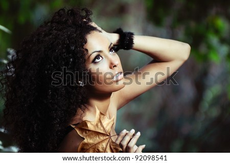 Portrait of a young black woman in the park with a dry leaf - stock photo