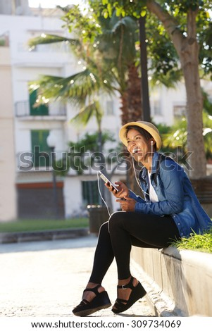 Portrait of a young black woman laughing and listening to music on cell phone - stock photo
