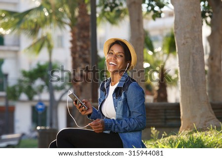 Portrait of a young black woman laughing with mobile phone - stock photo